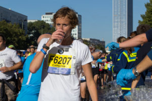 Frau trinkt bei Laufveranstaltung