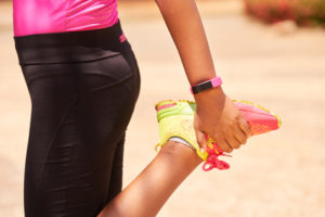 Young Woman Sports Stretching Using Fitwatch Steps Counter