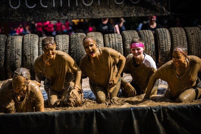 Teilnehmer des Muddy Angels Runs im Schlammbecken.
