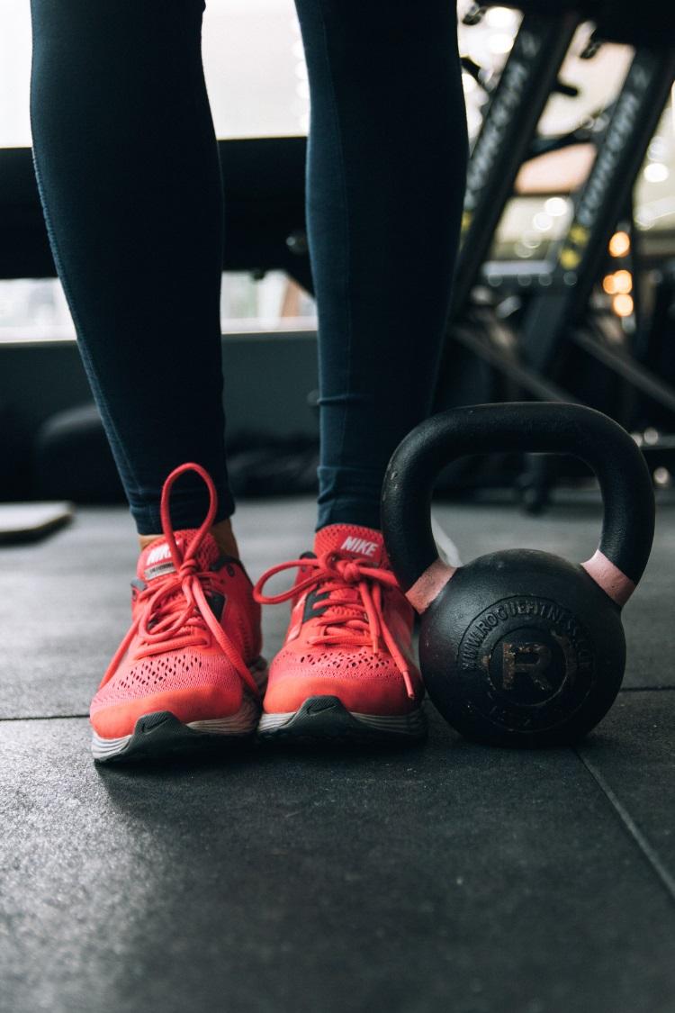 frau-fitnessstudio-mit-roten-sportschuhen
