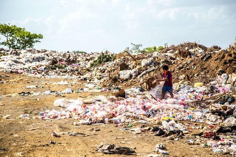 kind sortiert plastikmüll in einem großen müllberg