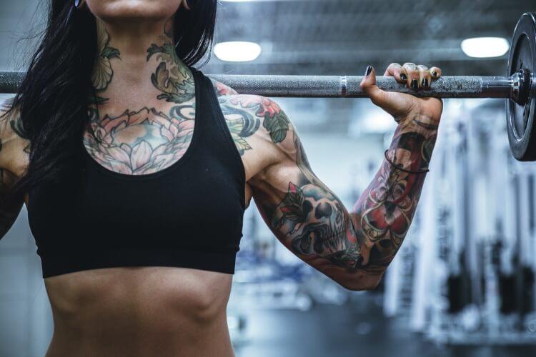 Frau trainiert im Gym mit Hantelscheiben.